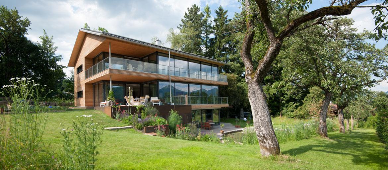 Freistehendes Haus mit Glasfront und Holz mit Blick in großen Garten