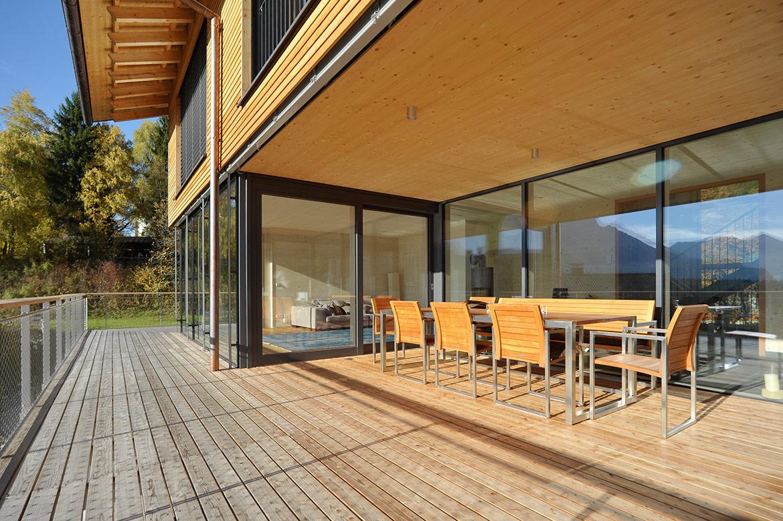 Blick vom Balkon mit Tisch und Stühlen durch eine Glasfront ins Haus
