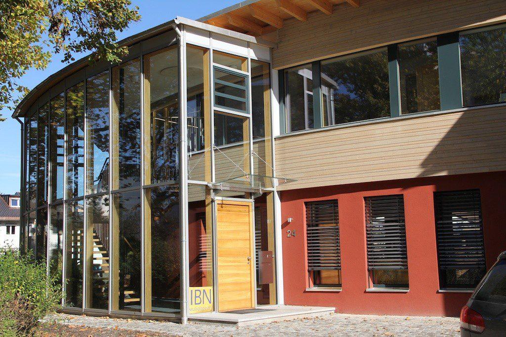 Gebogene Glasfassade mit Blick auf Eingangsbereich