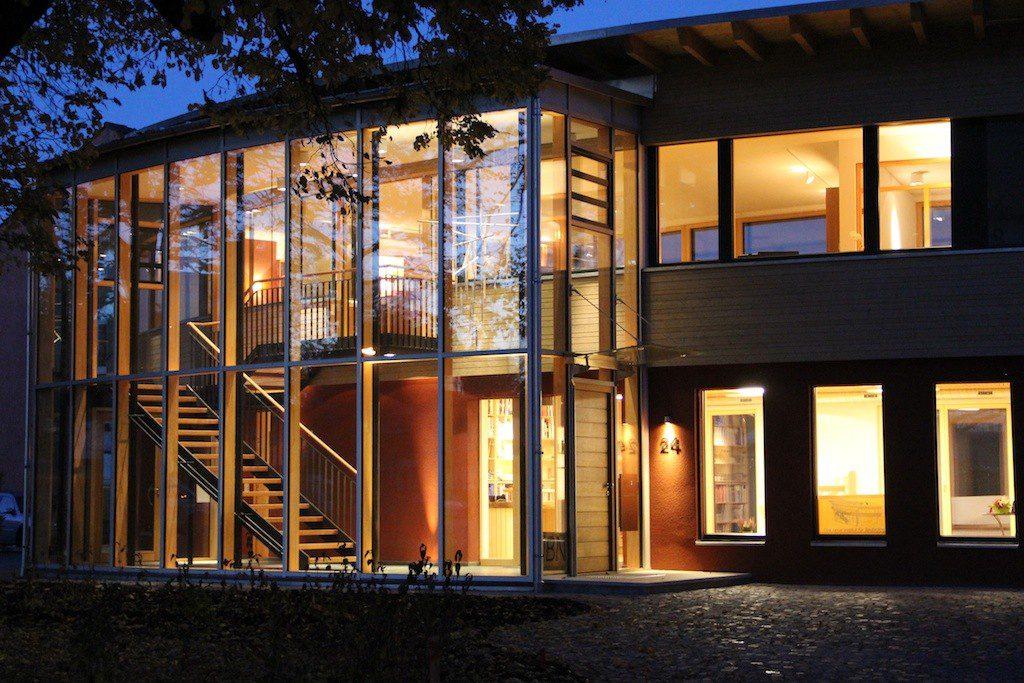 Gebogene Glasfassade mit Blick auf Eingangsbereich bei Nacht