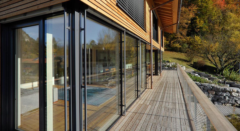 Passivhaus mit Holzbalkon mit Blick auf komplette Glasfront