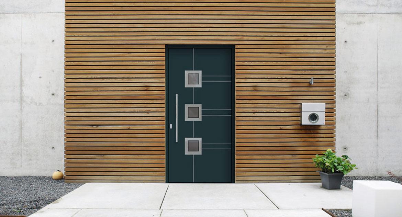 Grüne Tür mit drei Fenstern auf einer Hausfront mit Holzumrahmung